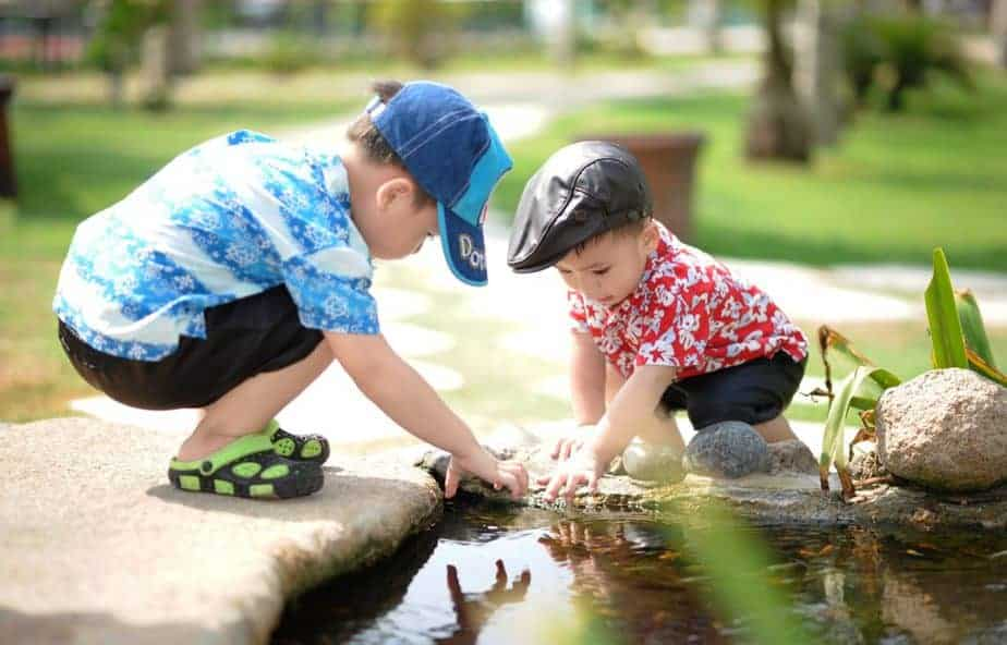 Two small boys playing in pond