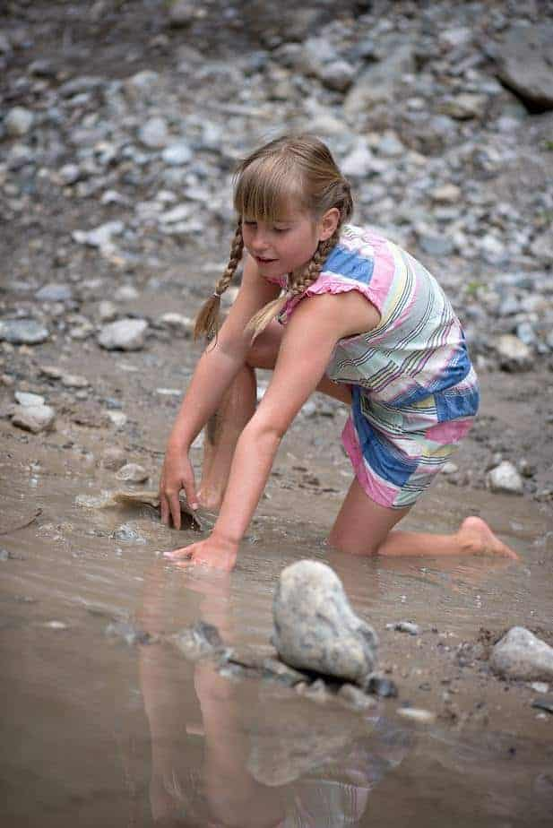 little girl playing at lakes edge