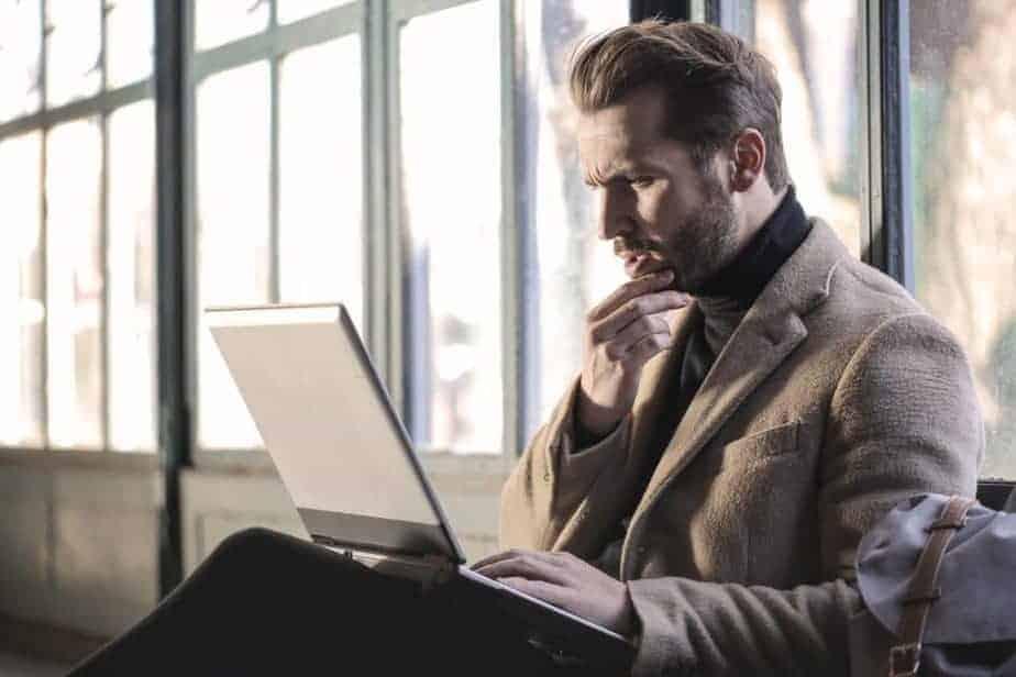 man sitting with laptop, pondering