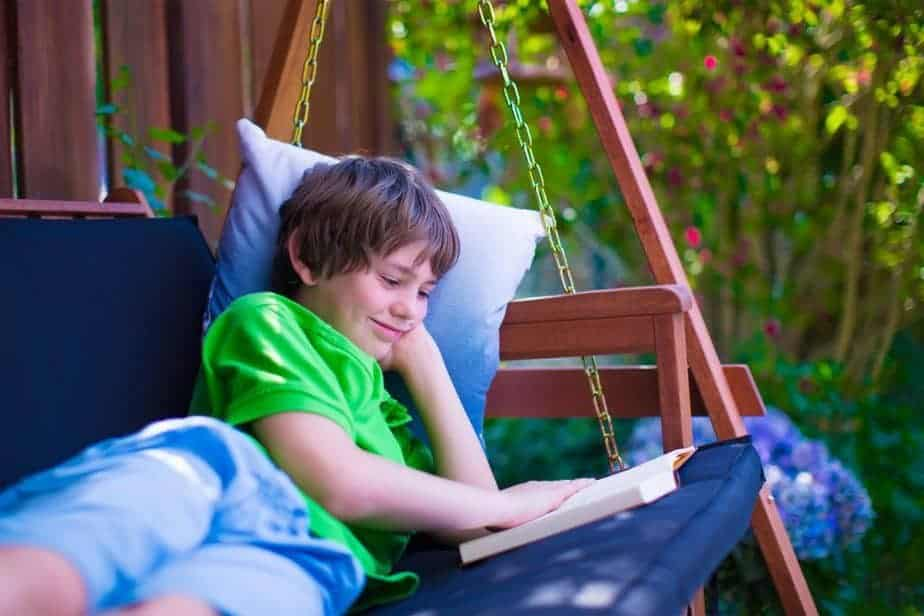 boy smiling while laying on swing, reading a book