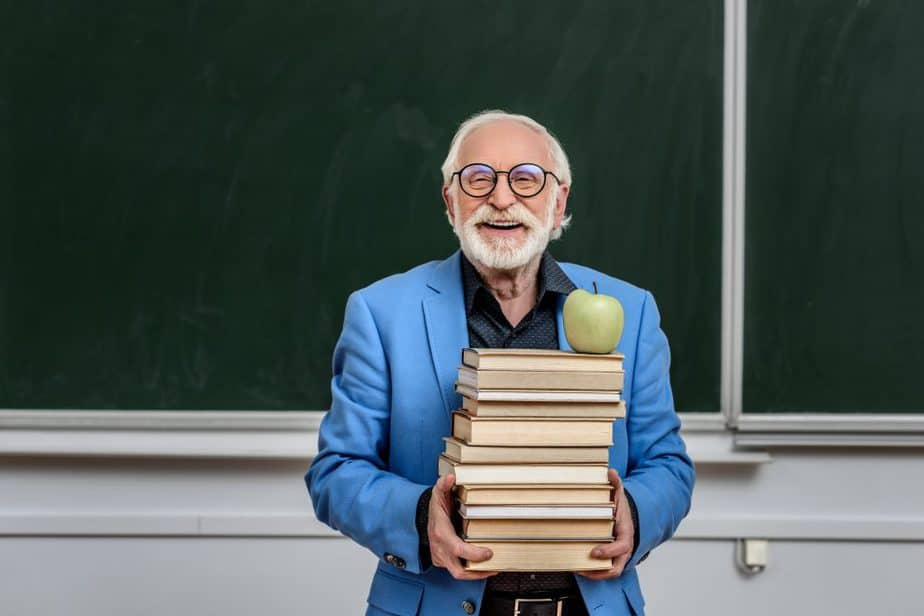 happy older man teacher holding stack of books with an apple on top in front of a chalkboard