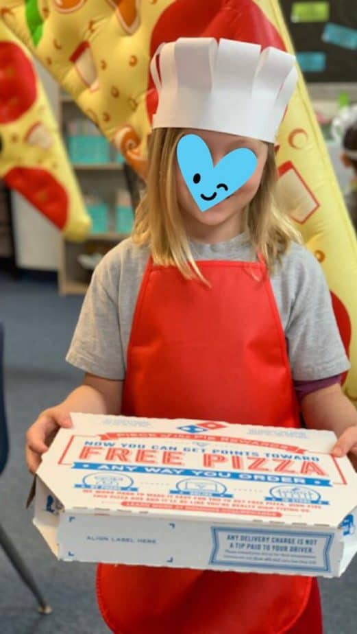 Little girl holding pizza box with apron and chef hat