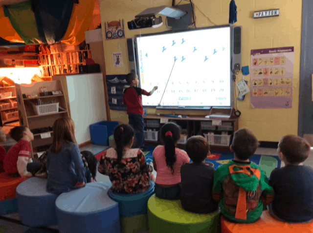students on flexible seating watching another child at the SmartBoard