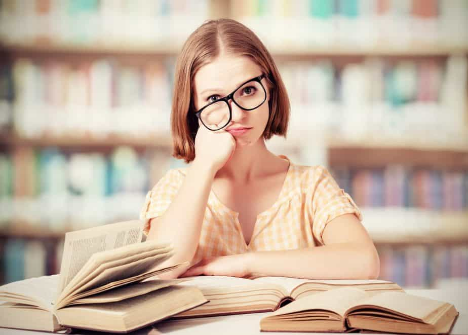 tired woman with crooked glasses reading books in the library