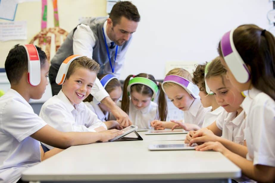 Group of children wearing colorful wireless headsets while working on digital tablets, the teacher can be seen supervising the students in the classroom