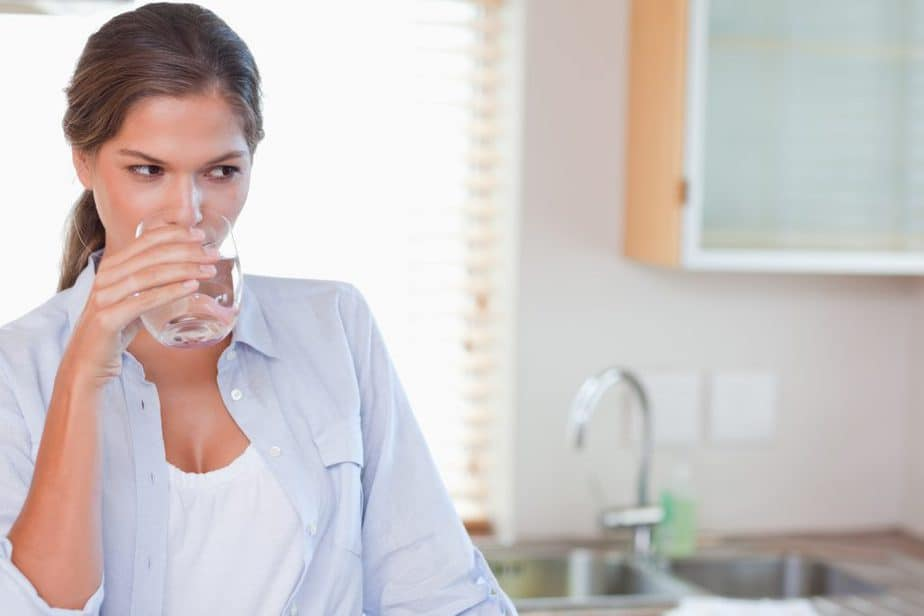 Woman drinking a glass of water in her kitchen